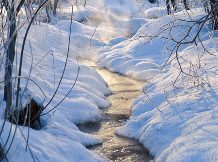 exhalation: Small winter stream with vapor over water in Sun rays under snow and ice in winter season. Novosibirsk, Russia