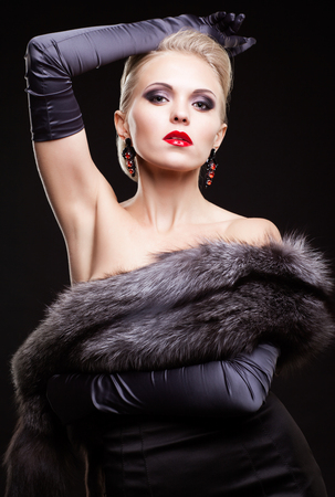 silver fox: Young blonde woman in black dress and silver fox fur with and long gloves on dark background Stock Photo