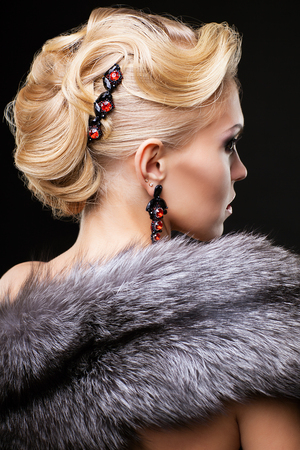 silver fox: Young blonde woman in black dress and fur of silver fox on dark background