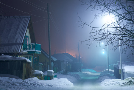 Night shot of country street under snow in winter season. Novosibirsk, Siberia, Russia Stock Photo