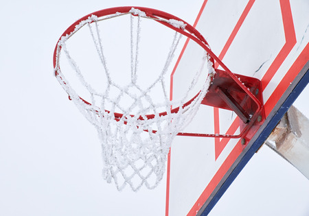 backboard: Outdoor basketball hoop with net, covered by hoarfrost Stock Photo