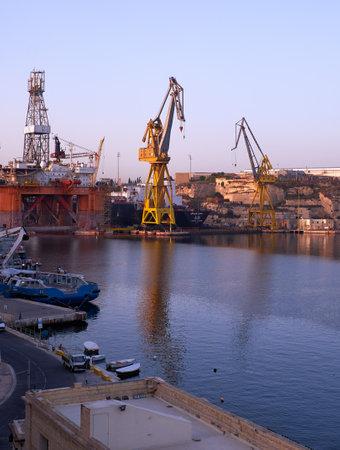dawning: COSPICUA, MALTA - AUGUST 1, 2015:  The Noble Paul Romano Oil rig in the Palumbo Shipyards in Cospicua (Bormla), Malta.