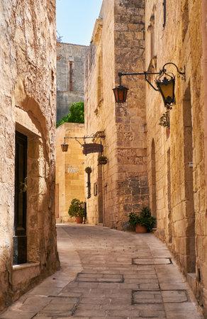 empedrado: Mdina, Malta - julio 29 de, 2015: La calle pavimentada piedra medieval estrecha con el restaurante Medina en el Mdina, la antigua capital de Malta.