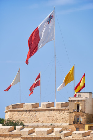 flatter: The flags of Malta, Sovereign Military Order of Malta, Vatican and Spain raised over the fortress walls of Post of Castile for the case of holiday. Malta