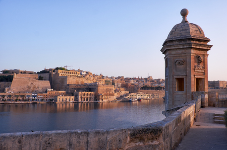 The early morning view of the Senglea Guard tower with sculpted symbols  (crane bird and ear) on the background of Grand harbour and Valletta. Senglea, Malta. Stock Photo
