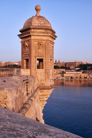The early morning view of the Senglea Guard tower with sculpted symbols  (crane bird, ear and nose) on the background of Grand harbour. Senglea, Malta.