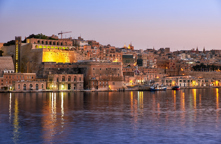 dawning: The early morning view of Valletta capital city fortifications with Fort Lascaris and Upper and Lower Barrakka Gardens  from the water of Grand Harbour. Malta Stock Photo