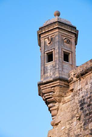 The Guard tower Gardjola on the end of Senglea  peninsula bastion with sculpted symbols  (eye, ear and nose) representing guardianship and observance protecting the Maltese shores. Senglea, Malta Stock Photo