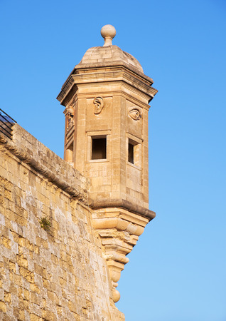 observance: The Guard tower on the end of Senglea peninsula bastion with sculpted symbols  (eye, ear crane bird and nose) representing guardianship and observance protecting the Maltese shores. Senglea, Malta.