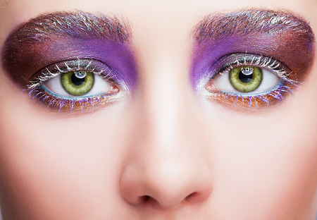 face shot: Closeup shot of female face with green pistachio colour eyes, evening violet purple eyes shadows and white eyelashes makeup
