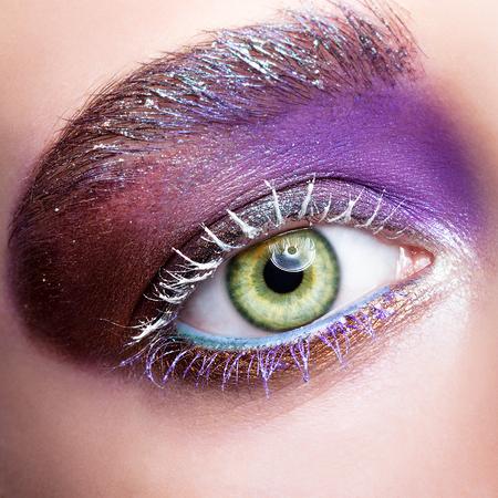 white colour: Closeup shot of female green pistachio colour eye  with evening violet purple  eyes shadows and white eyelashes makeup Stock Photo