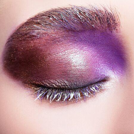 flashy: Closeup shot of female closed eye with evening violet purple eyes shadows and white eyelashes makeup