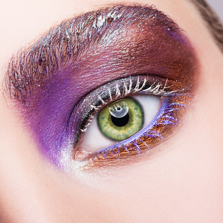 flashy: Closeup shot of female green pistachio colour eye  with evening violet purple  eyes shadows and white eyelashes makeup Stock Photo
