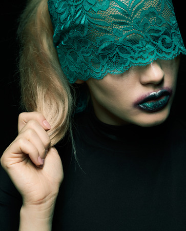 beauty eyes: Halloween beauty portrait of young beautiful woman with green lacy ribbon on eyes on black background Stock Photo