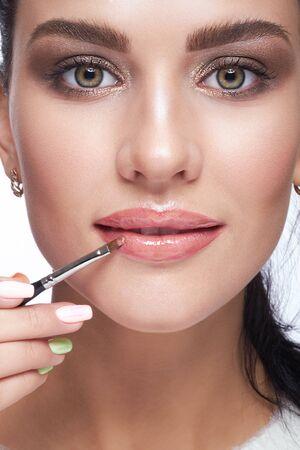 ojos marrones: Primer tirado de la mujer pintar sus labios con el lápiz labial cosmético del cepillo en los labios Foto de archivo
