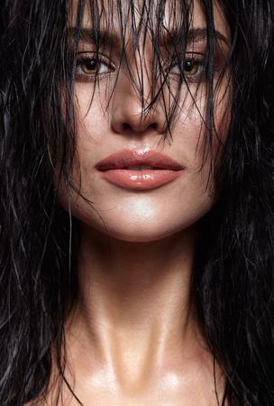 ojos negros: Retrato de una mujer joven morena con Hining húmeda maquillaje y peinado brillante pelo largo húmedo