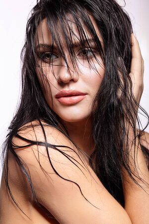 wild hair: Portrait of a young brunette woman with hining wet make-up and shiny moist long hair hairdo
