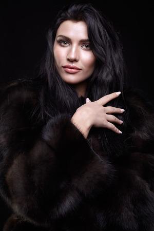 cabello negro: Retrato de una mujer joven morena con el pelo largo y negro vestido con un abrigo de piel sobre fondo negro