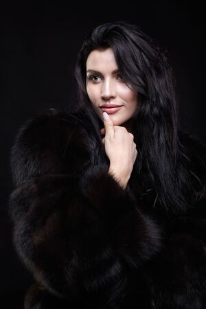 suntanned: Portrait of a young brunette woman with long black hair dressed in a fur coat on black background