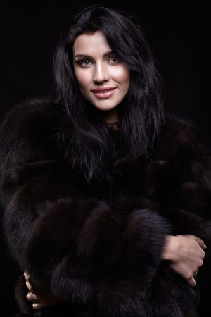 Portrait of a young smiling brunette woman with long black hair dressed in a fur coat on black background