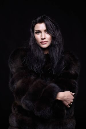 Portrait of a young brunette woman with long black hair dressed in a fur coat on black background