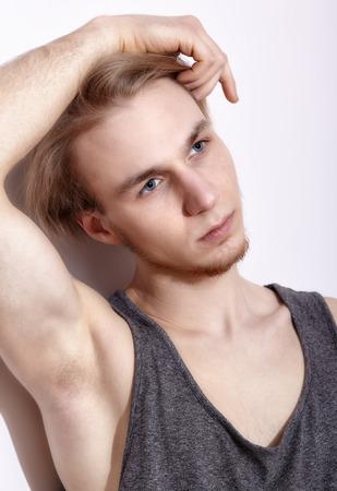 sexualidad: Joven rubia en camisa posando cerca de la pared blanca