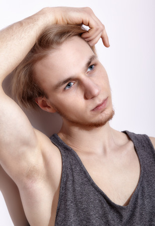 underarm: Young blonde man in shirt posing near white wall