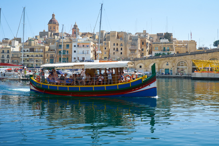 BIRGU, MALTA - JULY 23, 2015: The view of traditional Maltese boat Luzzu, serving as a walking  dinghy in Dockyard bay on the background of Birgu city. Malta