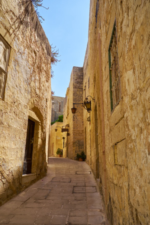 bowery: MDINA, MALTA - JULY 29, 2015: In the surroundings of limestone walls. The narrow medieval stone paved street of Mdina, the old capital of Malta
