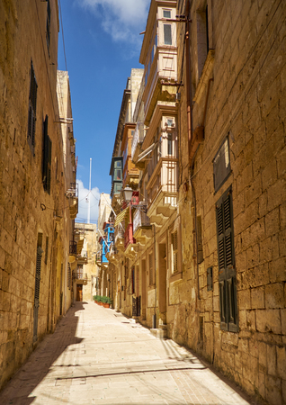 residential houses: In the sandstone surroundings. The narrow medieval stone paved street and residential houses of Valletta, the capital of Malta.