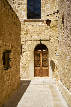 bowery: In the surroundings of limestone walls. The narrow medieval stone paved street of Mdina, the old capital of Malta