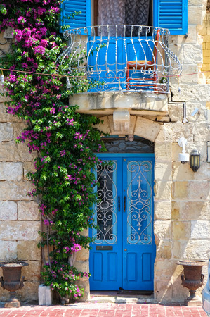 The view of beautiful Maltese style door and balcony entwined with bougainvillea on Birgu. Malta Stock Photo