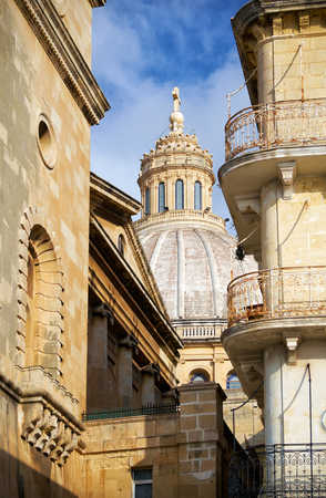 The view of dome of Basilica of Our Lady of Mount Carmel in the lumen of houses, Valletta, Malta