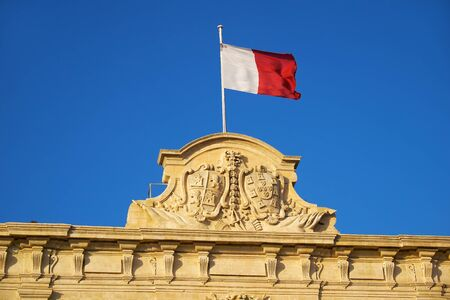 The decoration topped with a Maltese flag on the roof of the Auberge de Castille (now office of the Prime Minister of Malta) with the coats of arms of Castile and Leon and Portugal. Valletta, Malta
