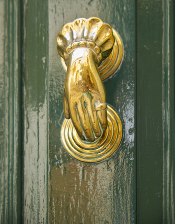 An old style decorative bronze door handles in the form of a womans hand, the distinctive feature of Malta. Stock Photo