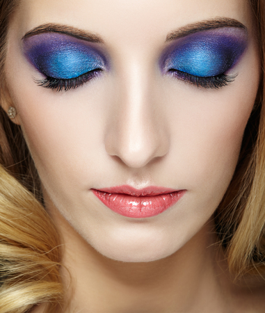 face shot: Closeup shot of female face with closed eyes with blue and violet makeup