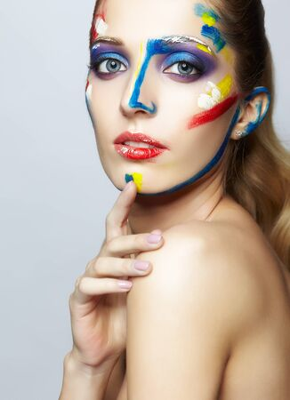 Young woman painter with  acrylic paint on face Stock Photo