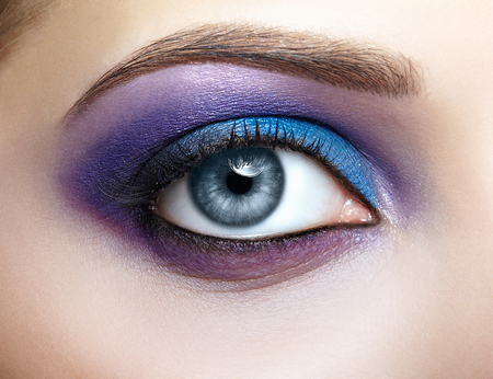 青と紫のメイクと女性の目のクローズ アップ