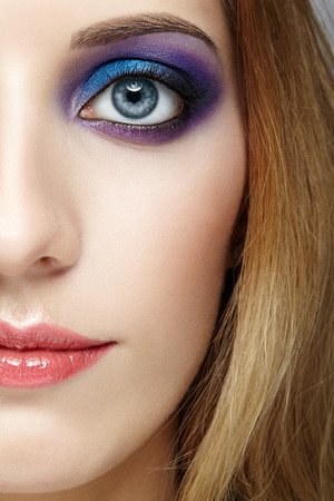 face shot: Closeup shot of female half face with  and violet and blue eyes makeup