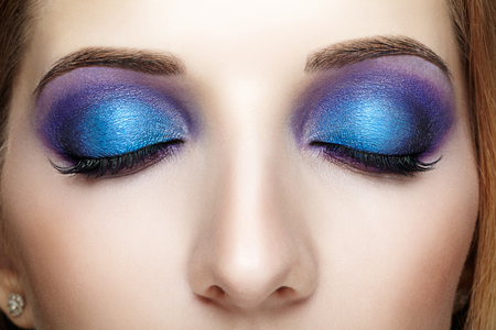 face shot: Closeup shot of female face with closed eyes and blue - violet makeup
