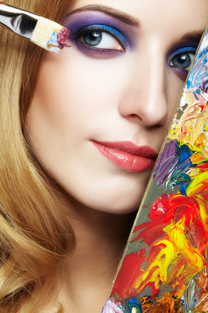 Young woman painter with color palette and paint brush in hand Stock Photo