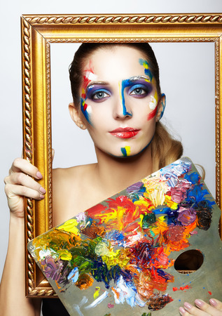 grey eyed: Young woman painter in golden frame with color palette in hand Stock Photo