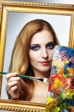 grey eyed: Young woman painter in golden frame with color palette and paint brush in hand