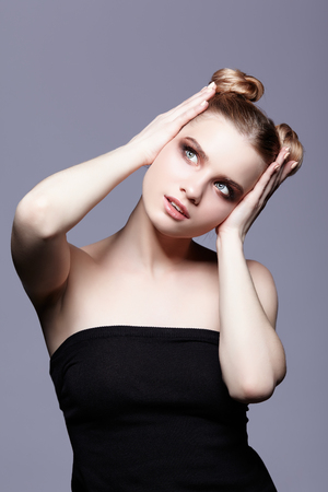 smoky black: Young teen female beauty portrait with day makeup and bun hair style  on grey background