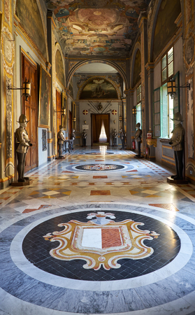 VALLETTA, MALTA - JULY 31, 2015: The view of the armoury corridor on the main floor of the Grandmasters Palace with the Coat of arms of Malta on the foreground. Valletta. Malta