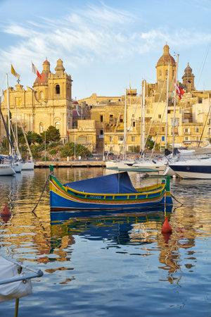 VALLETTA, MALTA - JULY 31, 2015: The Maltese boat (luzzu) moored in the harbor of Dockyard creek in front of Birgu waterfront. Birgu, Malta.