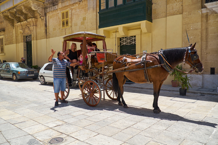 taxista: MDINA, MALTA - JULY 29, 2015:  The cabby gives a tour to the tourists sitting in the horse carriage on the St Pauls Square, Mdina, Malta. Editorial