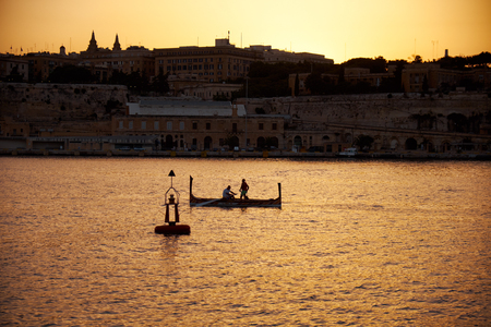 The early morning view of two people sailing  in a traditional Maltese boat (luzzu) near the buoy along the Grand harbor with Valletta on background. Malta