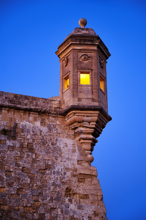 The early morning  view of Guard tower on the end of Senglea (L-isla) peninsula bastion with sculpted symbols  (eye, ear and nose) representing guardianship and observance protecting Malta
