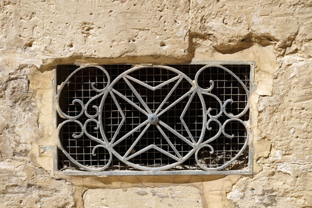 The decorative  metal ventilation grill in form of 8-pointed Maltese cross in a stone wall. Rabat. Malta